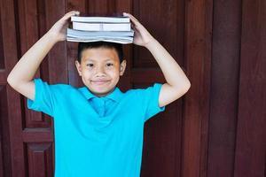 jongen met boeken op het hoofd
