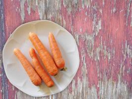 wortelen op een witte plaat op een houten tafel achtergrond foto