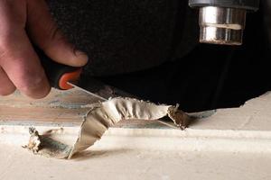 handen schoonmaken van deuren van oude verf met een spatel, herstel reparatie close-up