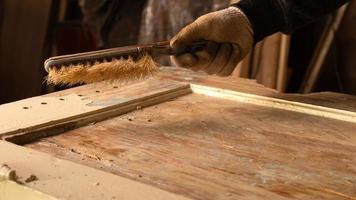 handen schoonmaken van oude verf van een houten deur, restauratie van houten meubilair