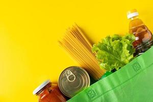 levering van noodzakelijk voedsel tijdens quarantaine. donatie levensmiddelen op een gele achtergrond.