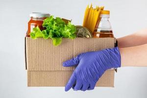 een vrouwelijke vrijwilliger houdt een donatiebox met etenswaren vast. levering van noodzakelijk voedsel tijdens een epidemie.