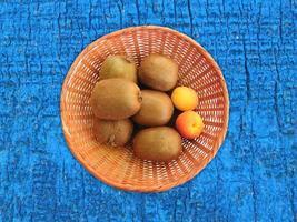 kiwi's en abrikozen in een rieten mand op een houten tafel achtergrond foto