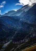 wolken op de top van de rotsachtige bergen