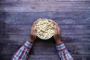 bovenaanzicht van iemands hand met een kom popcorn