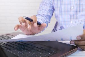man aan het werk met pen en papier
