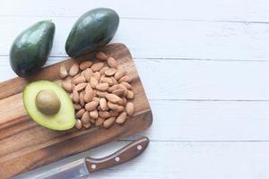 gehalveerde avocado en amandelen op snijplank