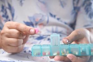 vrouwenhanden die medicijnen uit een pillendoosje nemen foto