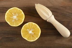 gesneden citroen met een houten ruimer op een houten tafel