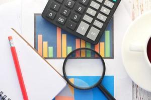 financiële grafiek, vergrootglas en notitieblok op tafel