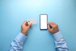 man hand met creditcard en met behulp van slimme telefoon online winkelen