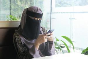 moslimvrouwen met hoofddoek binnenshuis met behulp van slimme telefoon foto