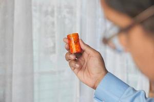 persoon die een pillenfles omhoog houdt foto