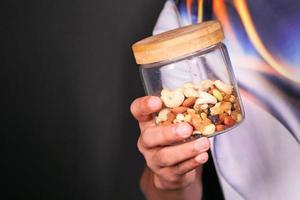 hand met een potje gemengde noten op zwarte achtergrond