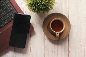 slimme telefoon en koffie op neutrale achtergrond