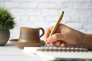 close-up van vrouw schrijven in Kladblok foto
