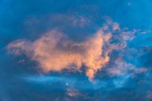 enkele wolk op een blauwe hemel die in roze gloeit van de ondergaande zon foto