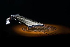 ongebruikelijke weergave van een akoestische gitaar verlicht en gloeiend in het donker
