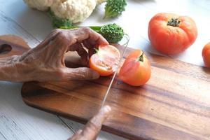 vrouw tomaten snijden op houten snijplank