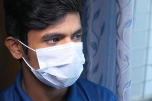 close-up van de man met een gezichtsmasker kijkt uit een raam