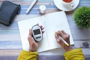senior vrouw met glucosemeter en schrijven in een planner