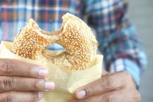 persoon die een bagel met sesamzaad eet