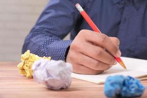 verkruimelde papieren op een bureau met een man aan het schrijven