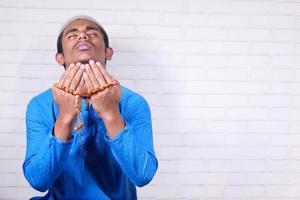 man bidden met kralen tegen neutrale achtergrond foto