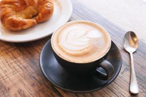 koffie en croissant op houten tafel foto