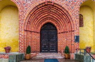 extreem gewelfde toegang tot een oude bakstenen kerk in Zweden foto