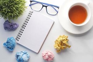 afgebrokkelde papieren op een bureau met een leeg notitieboekje