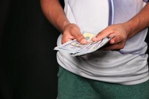 man geld tellen op zwarte achtergrond