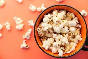 popcorn in een kom op oranje bovenaanzicht als achtergrond foto