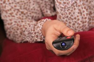 persoon met afstandsbediening van de tv