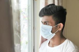 een jonge man met beschermend masker kijkt door raam