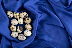verse boerderij kwarteleitjes op een blauwe satijnen doek