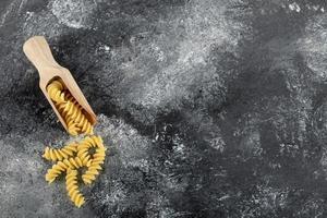 houten lepel rauwe fusilli op een marmeren achtergrond foto