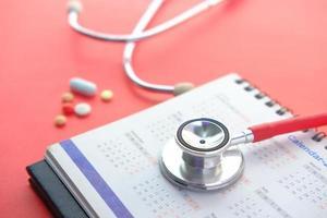 medische afspraak concept met stethoscoop en kalender op rode tafel foto