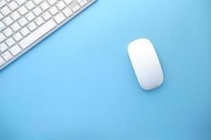 bovenaanzicht van computermuis en toetsenbord op blauwe achtergrond