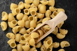 rauwe zeeschelpvormige pasta op een zwarte achtergrond foto