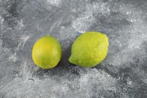 twee groene verse citroenen op een marmeren achtergrond foto