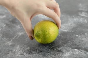 vrouw hand met een groene verse citroen