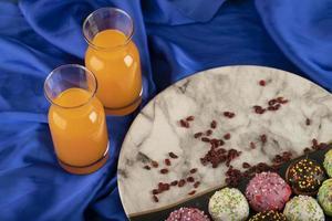 kleurrijke zoete kleine donuts met flessen sinaasappelsap foto