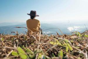 vrouw zittend op een berg gedurende de dag