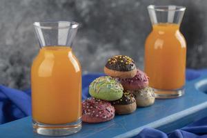 kleurrijke zoete donuts met glazen potten sap foto