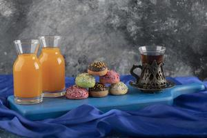 kleurrijke zoete donuts met glazen potjes sap en een kopje thee foto