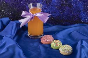 kleurrijke set van zoete kleine donuts met een glazen pot met sap foto