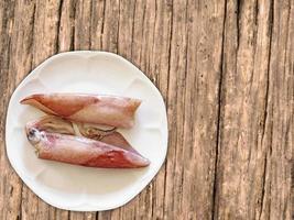 inktvis op witte plaat op houten tafel achtergrond foto