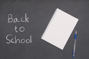 een wit notitieboekje met een pen op een schoolbord, terug naar school en onderwijsconcept