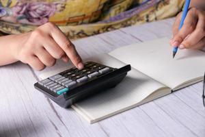 vrouw hand met behulp van rekenmachine op bureau foto